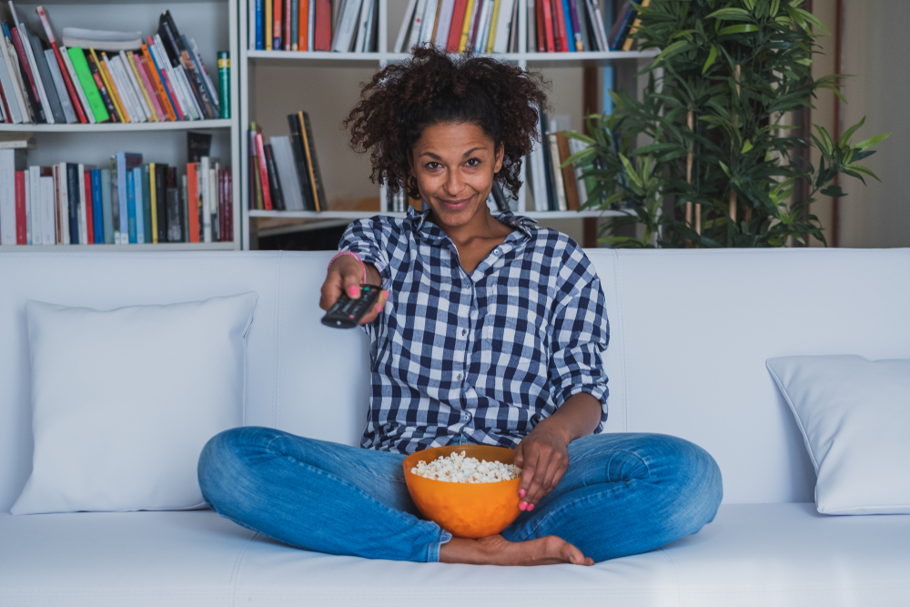 Shutterstock_1201292863 Happy woman sitting at home with remote control watching tv
