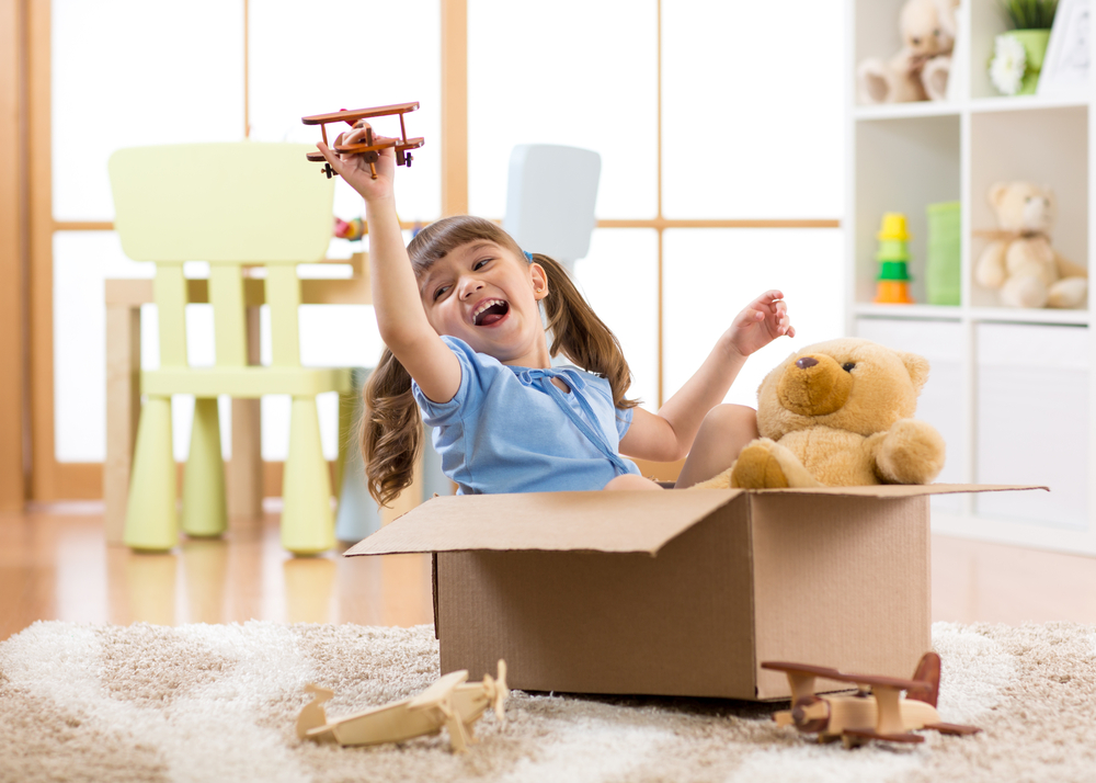 Shutterstock_633432545 Kid girl playing pilot flying a cardboard box in children room