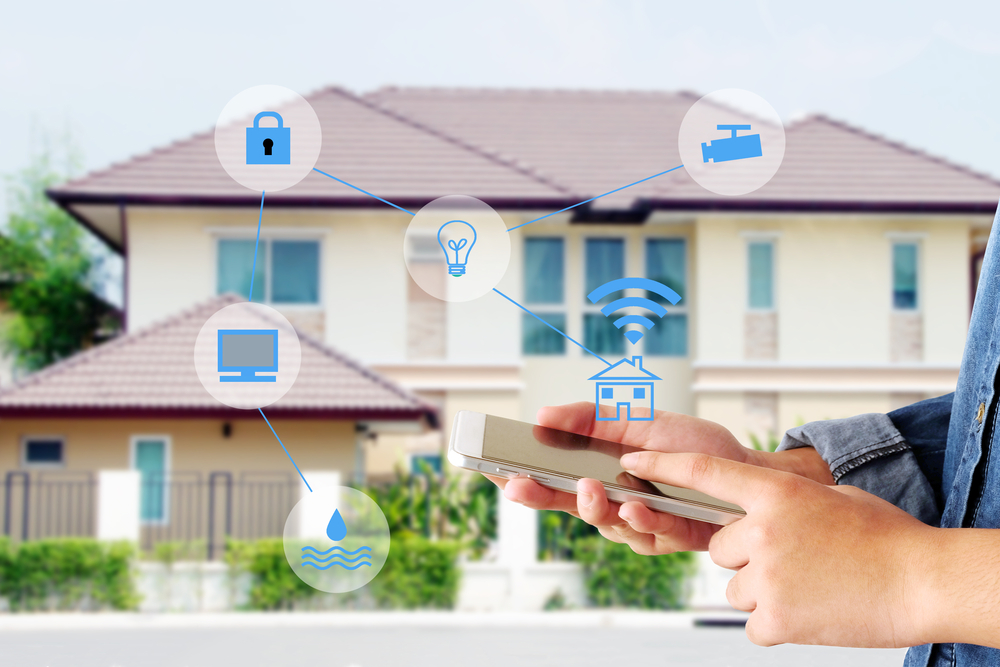 Shutterstock_593310095 Smart home secured automation with wifi technology, Hand using smartphone as house mobile monitor such as camera, computer, door and light, internet of things, people and smart home concept