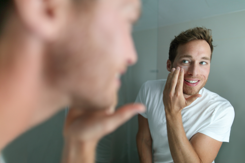 Shutterstock_790243321 Face cream young man putting skincare beauty product on face hydrating skin. Male beauty facial treatment care at home lifestyle. Person applying moisturizer for dry skin during winter.