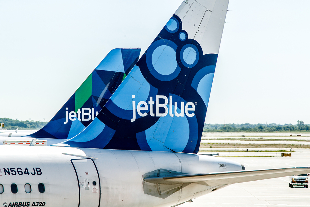 Shutterstock_674776387 Two JetBlue airplanes are parked by the gates awaiting passenger boarding.