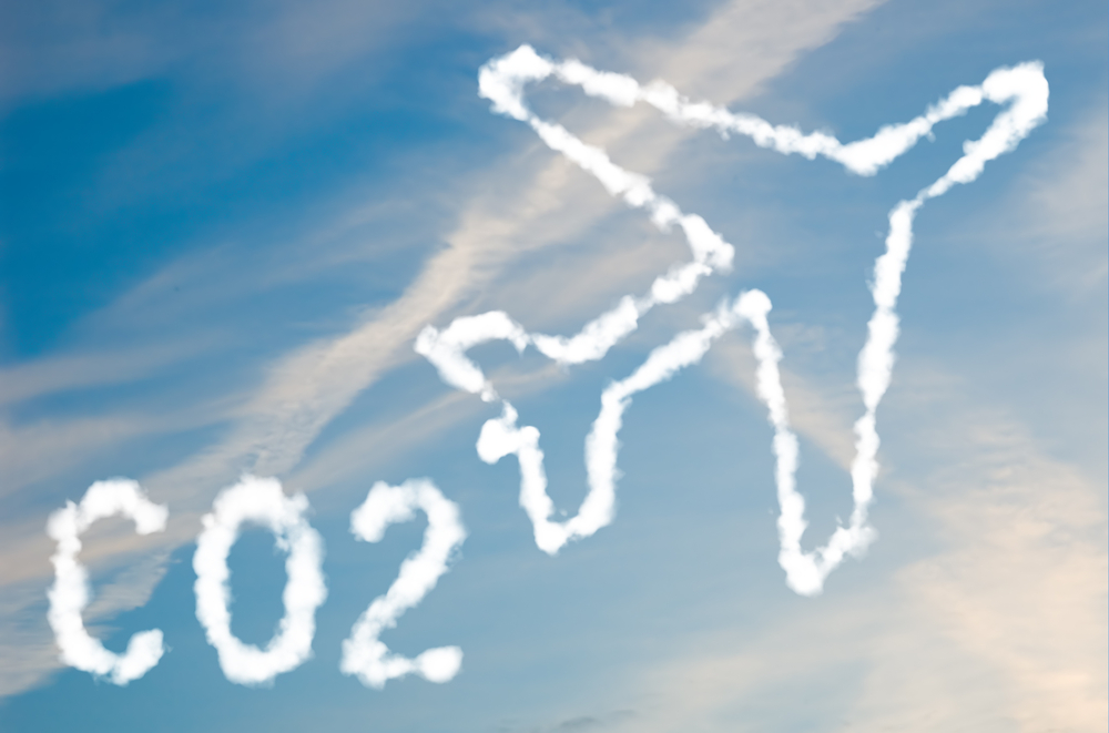 Shutterstock_48670516 An illustration of an airplane with the text CO2 made up of white puffy clouds to represent environmental issues or carbon footprint.