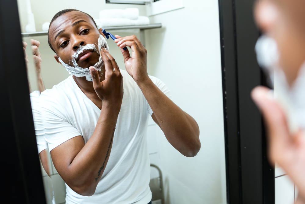 Shutterstock_448139398 Portrait of handsome young black man shaving in home bathroom.