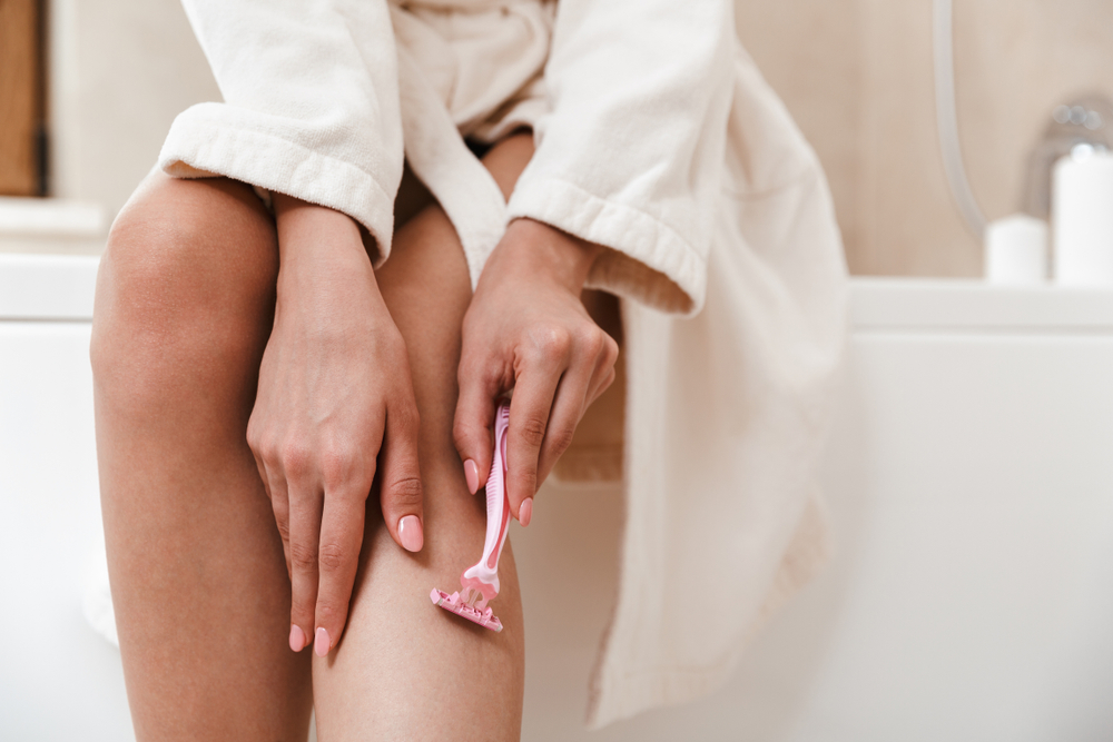 Shutterstock_1160003743 Photo of young woman in bathroom shaving her legs.