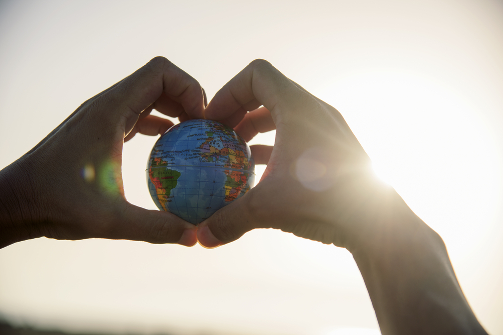 Shutterstock_700077757  closeup of a young caucasian man with a world globe in his hands forming a heart against the sky and a ray of sun showing up on the right