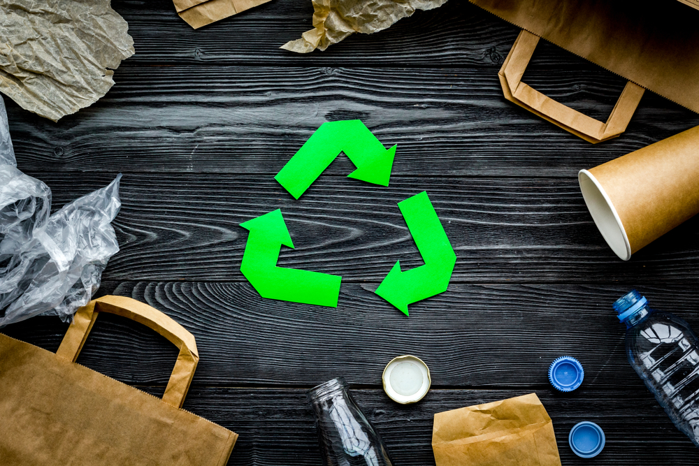 Shutterstock_1011996400 Eco-friendly life. Green paper recycling sign among waste paper, plastic, glass, polyethylene on grey wooden background top view