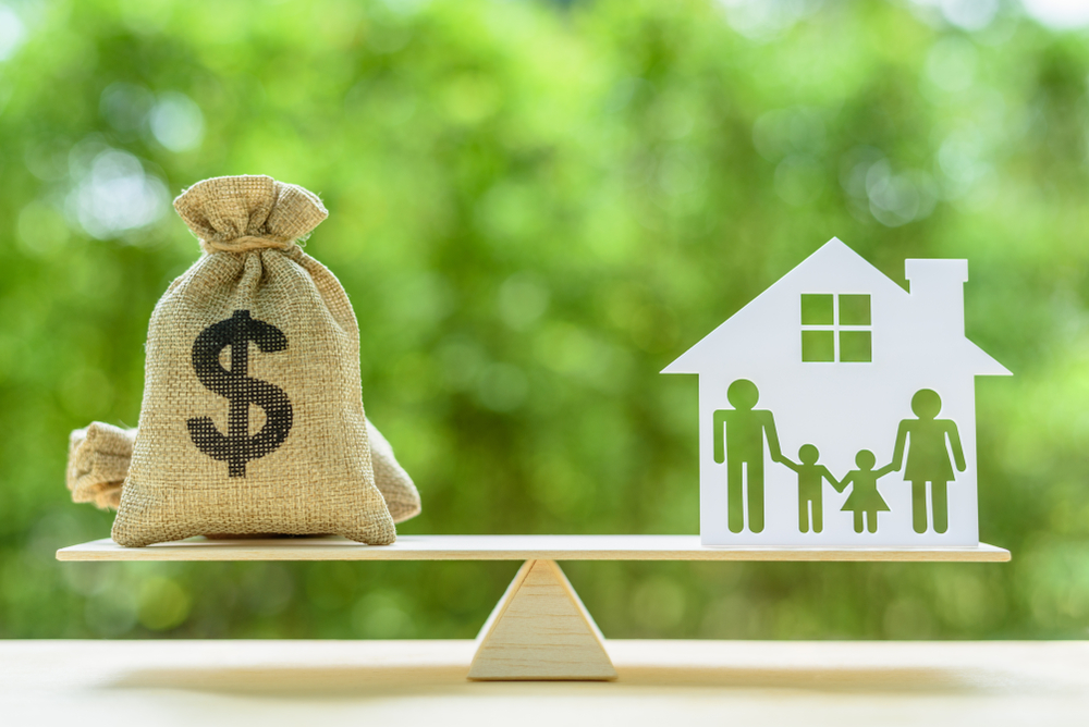 shutterstock_1178255803 Family financial management, mortgage and payday loan or cash advance concept : Dollar bags, 4 members family under a house or shelter on a balance scale, depicts short term borrowing for a residence.