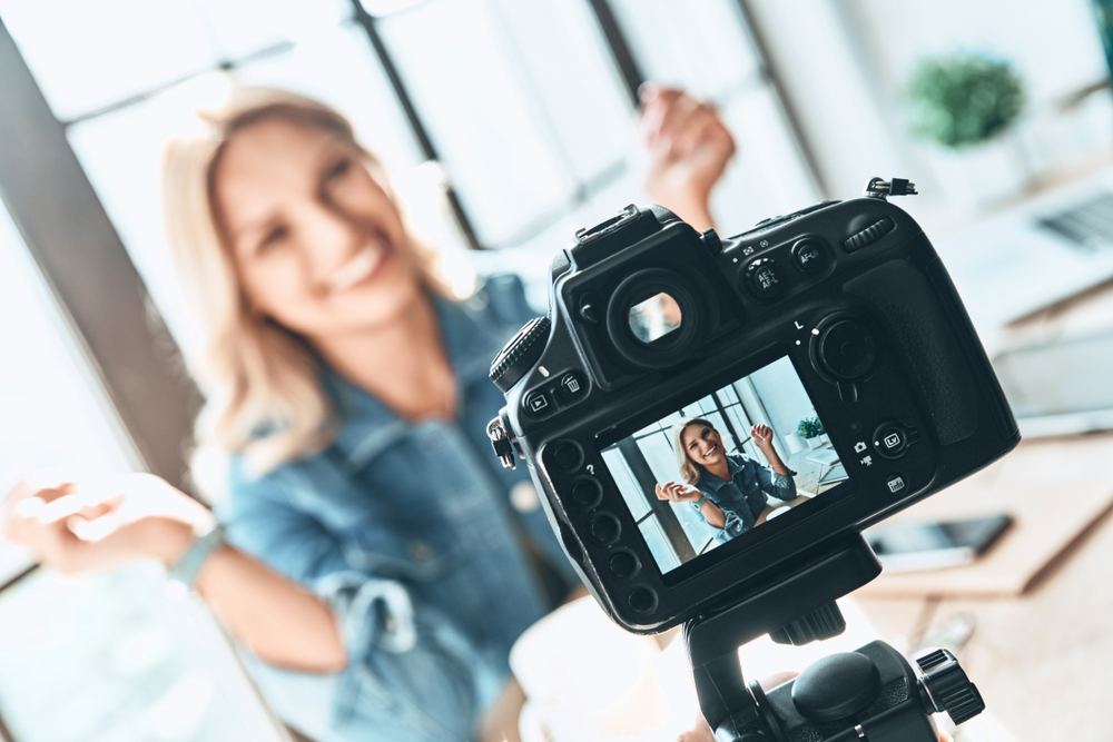 shutterstock_1099279586  Filming. Beautiful young woman in casual wear smiling while recording video