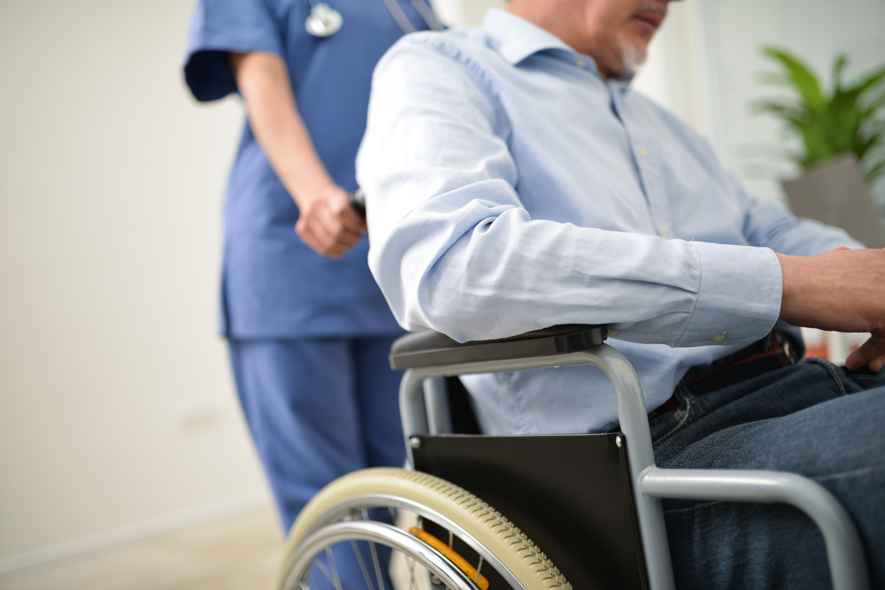 Shutterstock_417275146  Nurse pushing an injured patient on a wheelchair