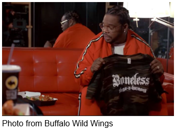 Man holding a shirt that says Bone Thugs-N-Harmony from Buffalo Wild Wings