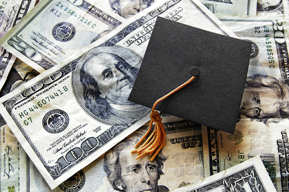 Shutterstock_398418100  Miniature graduation cap on hundred dollar bills