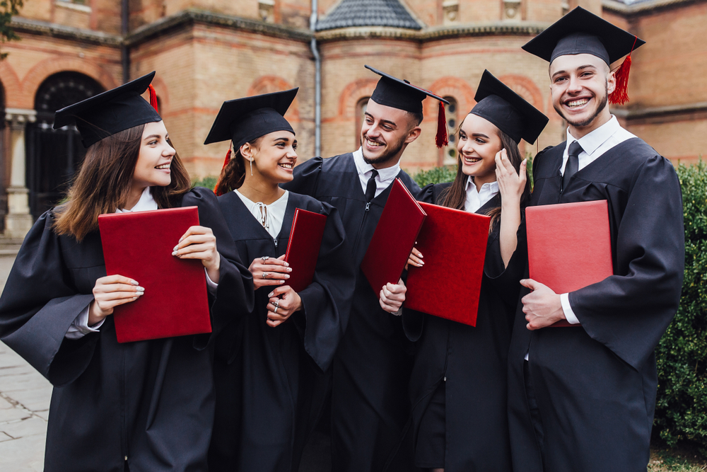 Shutterstock_1382310041  Graduates embrace, enjoy and look at the camera on the graduation ceremony!