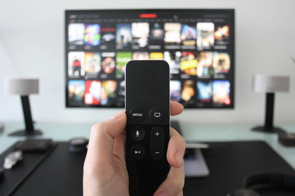 Shutterstock_1368793937  Hand holding a TV remote while watching shows on a streaming service on Television.
