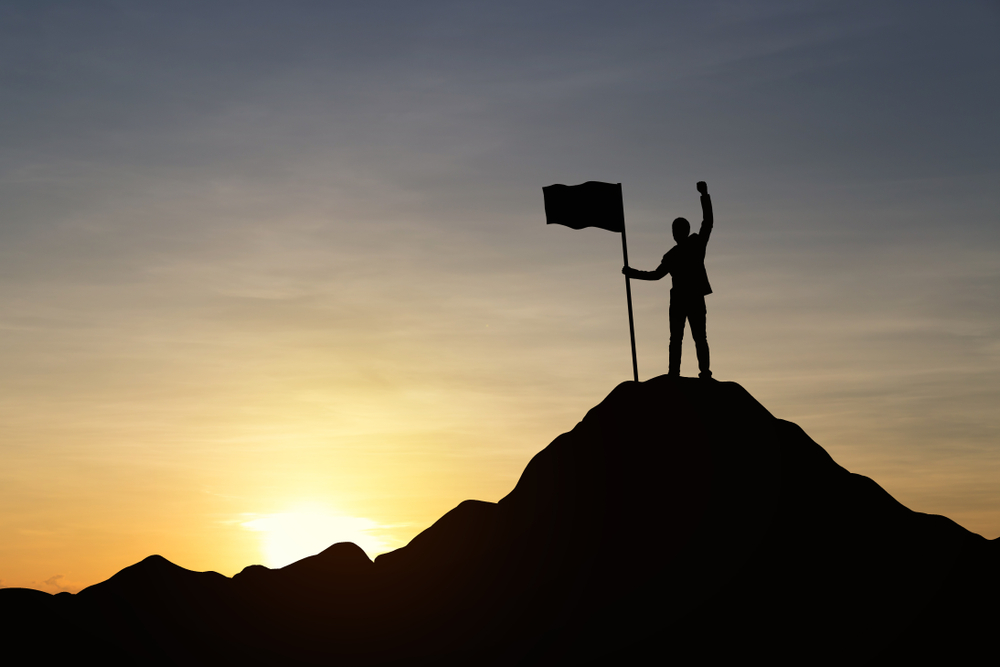 Shutterstock_766880638  Silhouette of businessman holding a flag on top mountain, sky and sun light background. Vintage filter. Business, success, leadership, achievement and goal concept.