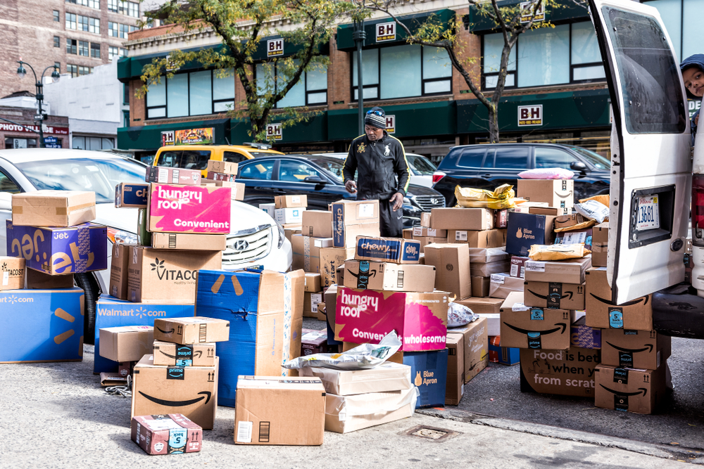 Shutterstock_1096584974  New York City, USA - October 30, 2017: Delivery man with many boxes in NYC by BH photo video store, van truck unloading amazon prime, walmart, chewy, blue apron