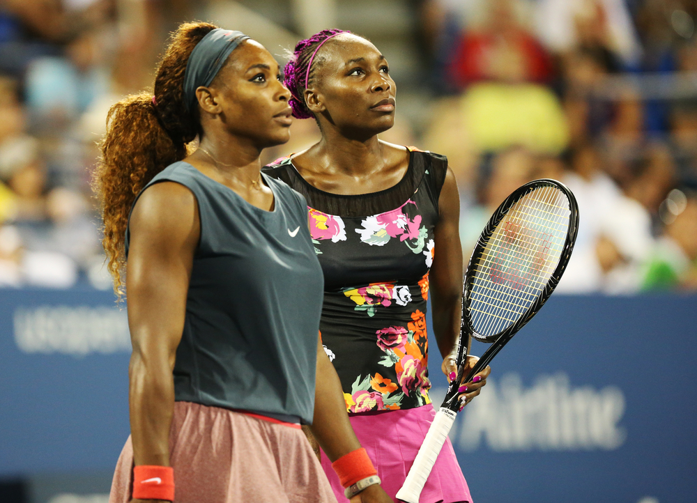 Shutterstock_328867460 NEW YORK - AUGUST 29, 2013: Grand Slam champions Serena Williams and Venus Williams during their first round doubles match at US Open 2013 at Billie Jean King National Tennis Center in New York