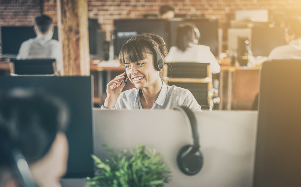 Shutterstock_739359772  Call center worker accompanied by her team. Smiling customer support operator at work. Young employee working with a headset.