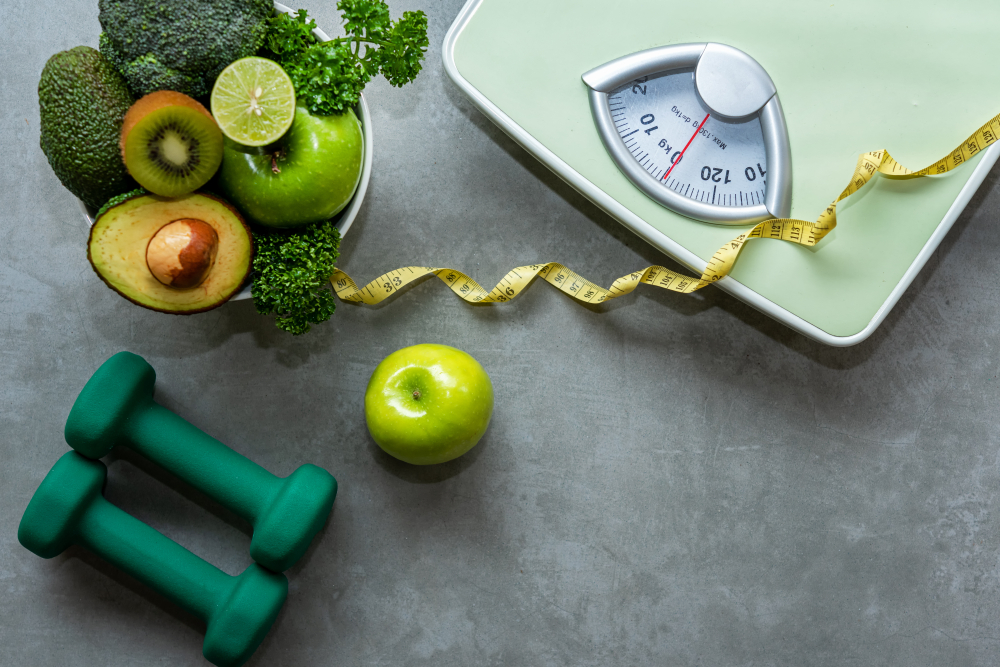 Shutterstock_1220319118 Diet and Healthy life loss weight slim Concept. Organic Green apple and Weight scale measure tap with nutrition vegan vegetable and sport equipment gym for body women diet fit. Top view copy space.