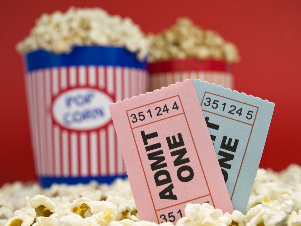 Shutterstock_27060235 Two popcorn buckets over a red background. Movie stubs sitting over the popcorn.