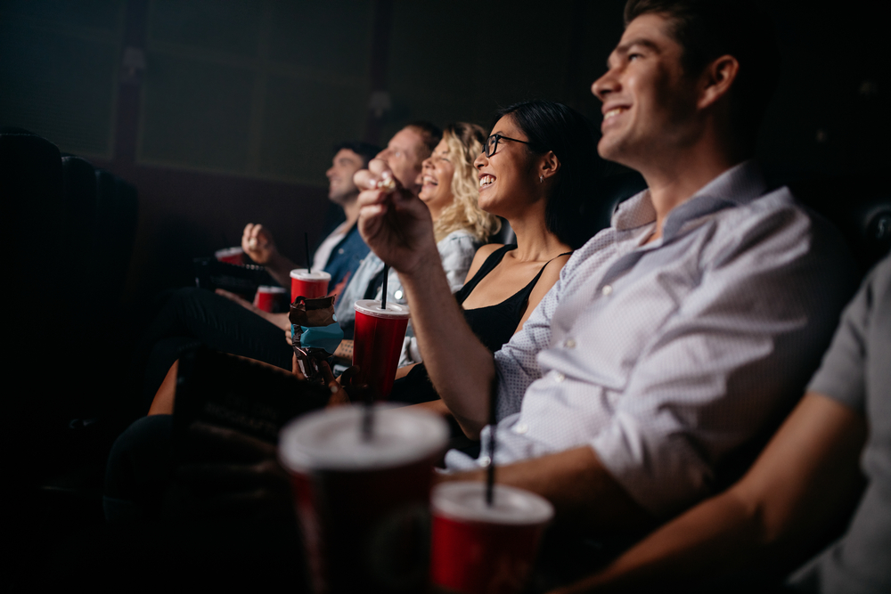 Shutterstock_518102128 Group of people in theater with popcorn and drinks. Young friends watching movie in cinema.