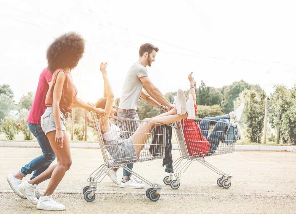 Shutterstock_1109615330  Young millennials people racing with shopping cart - Happy crazy friends having fun with trolleys in car park - Youth lifestyle and party concept - Focus on right guys