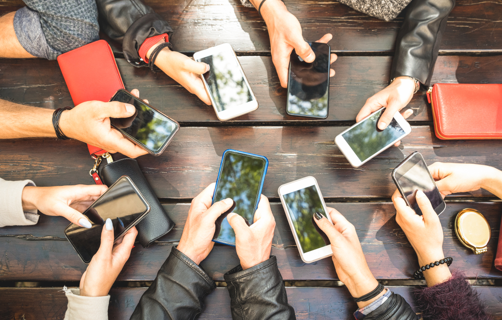Shutterstock_1071625919  People group having addicted fun together using smartphones - Detail of hands sharing content on social network with mobile smart phones - Technology concept with millennials online with cellphones