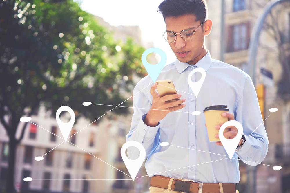 Shutterstock_1145893208  Serious student sending messages to friends in social network. Young male searching via app food restaurants near his location. Maps application for smartphone. Infographics tags with virtual map