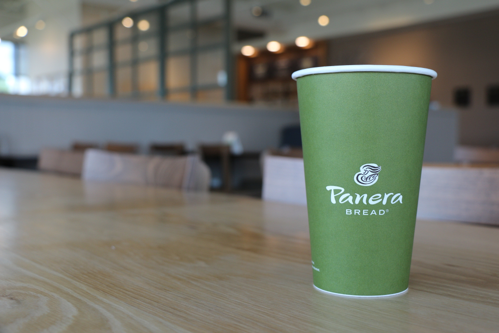 Shutterstock_1534687331  COLUMBUS, GEORGIA/USA - 06-20-2019 Green paper drinking cup with Panera Bread logo on a table at a Panera Bread restaurant in Columbus, GA.