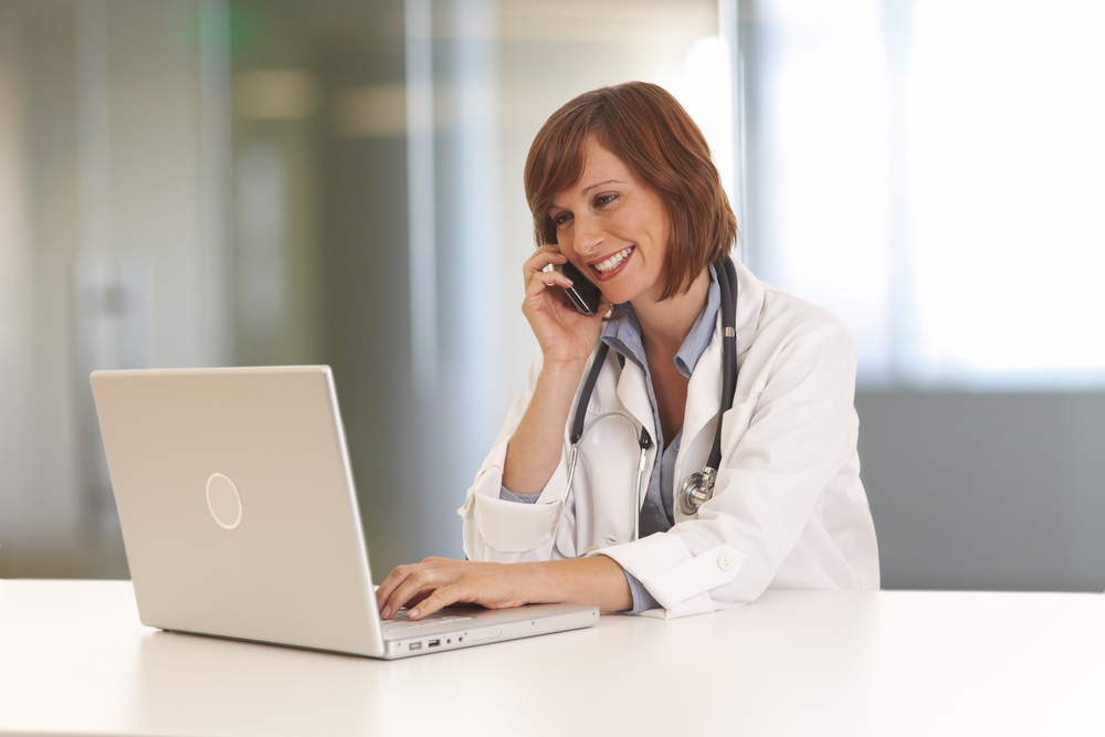 Shutterstock_71805475  Portrait of young woman doctor in white coat at computer using phone