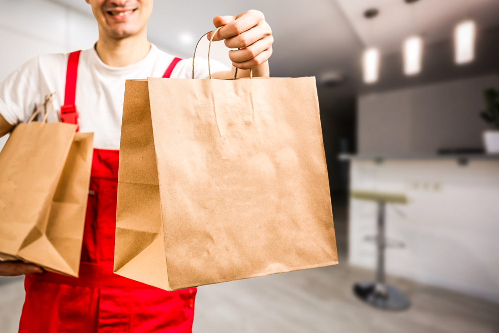 shutterstock_1459738184 Diverse of paper containers for takeaway food. Delivery man is carrying