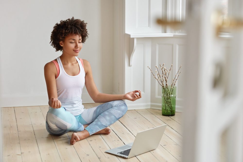 Shutterstock_1226534068 Calm lady with Afro hairstyle, dressed in sportswear, meditates on floor in empty room, listens spiritual practices lessons on laptop computer, poses in lotus pose, tries to relax. Yoga concept