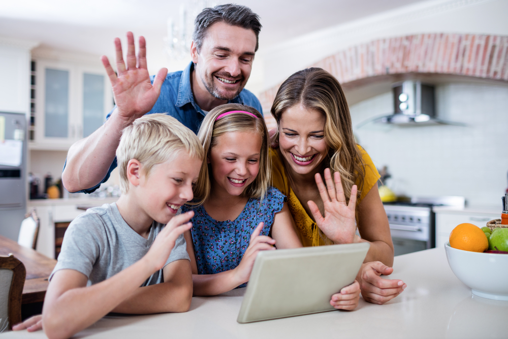 Shutterstock_572378356 Parents and kids waving hands while using digital tablet for video chat in kitchen