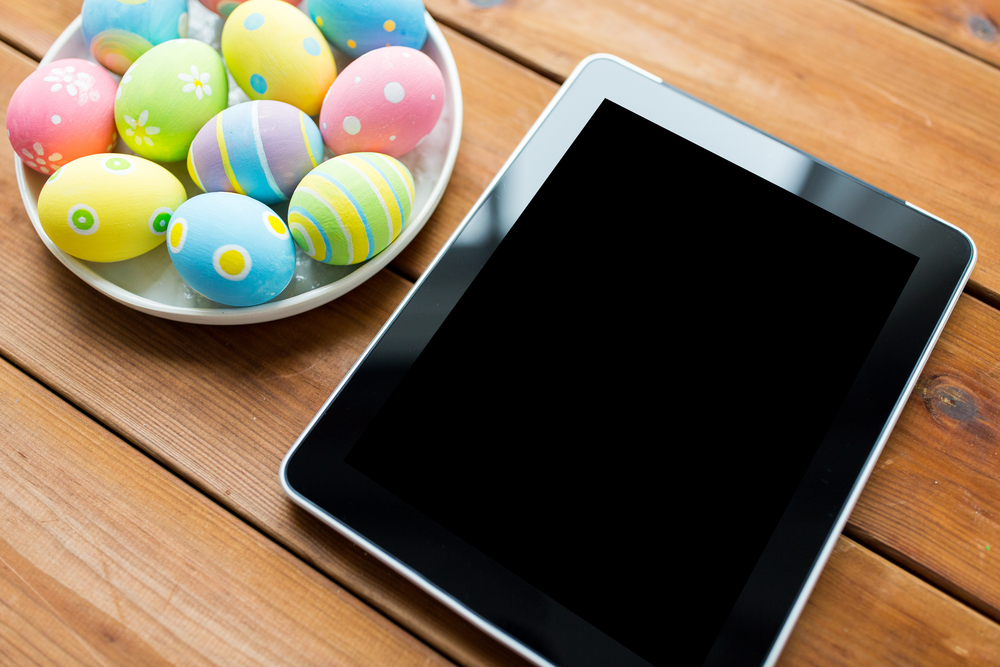Shutterstock_374875450 Easter, holidays, technology, advertisement and object concept - close up of colored easter eggs on plate and blank tablet pc computer