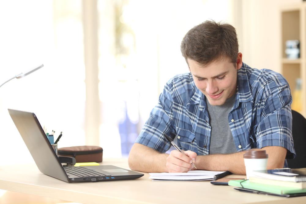 Shutterstock_360420464 Student studying and writing notes in a notebook sitting at a desk at home
