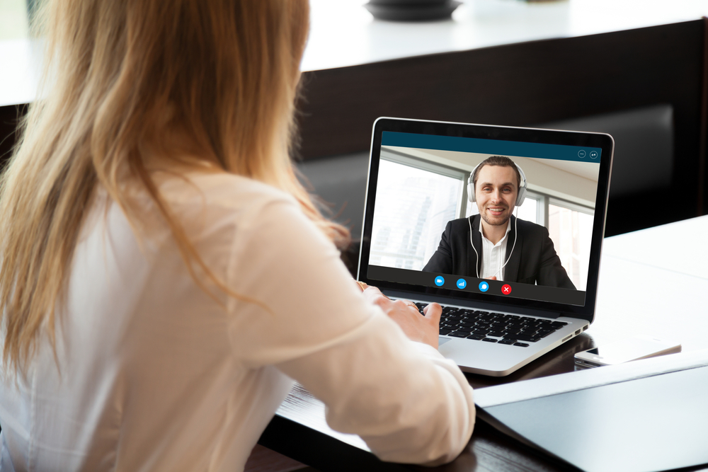 Shutterstock_749570365 Businesswoman making video call to business partner using laptop. Close-up rear view of young woman having discussion with corporate client. Remote job interview, consultation, human resources concept