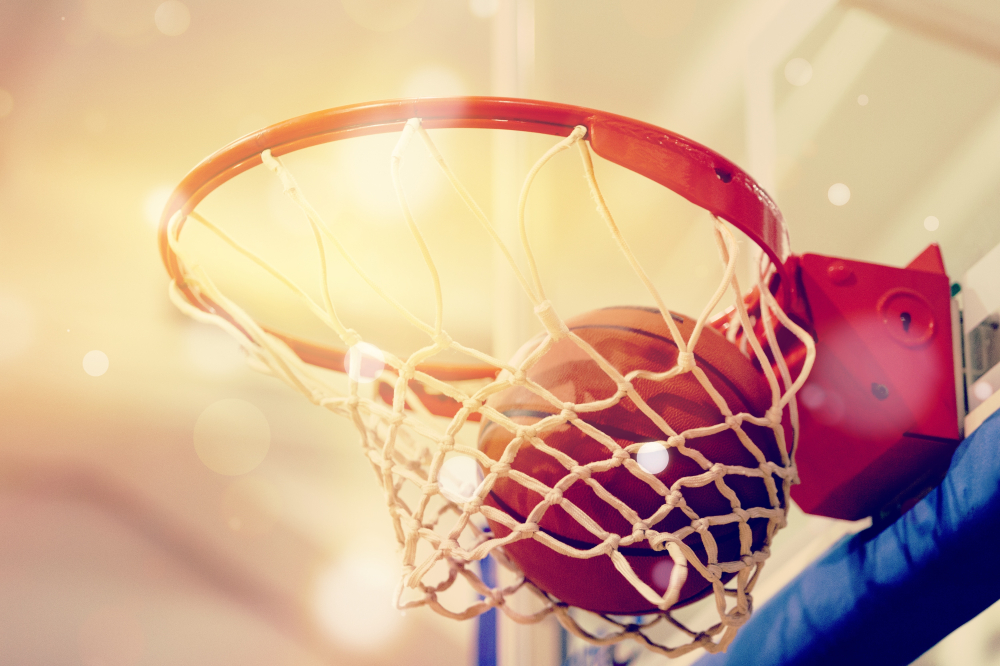 Shutterstock_1489878983 Orange basketball ball flying into the basketball hoop