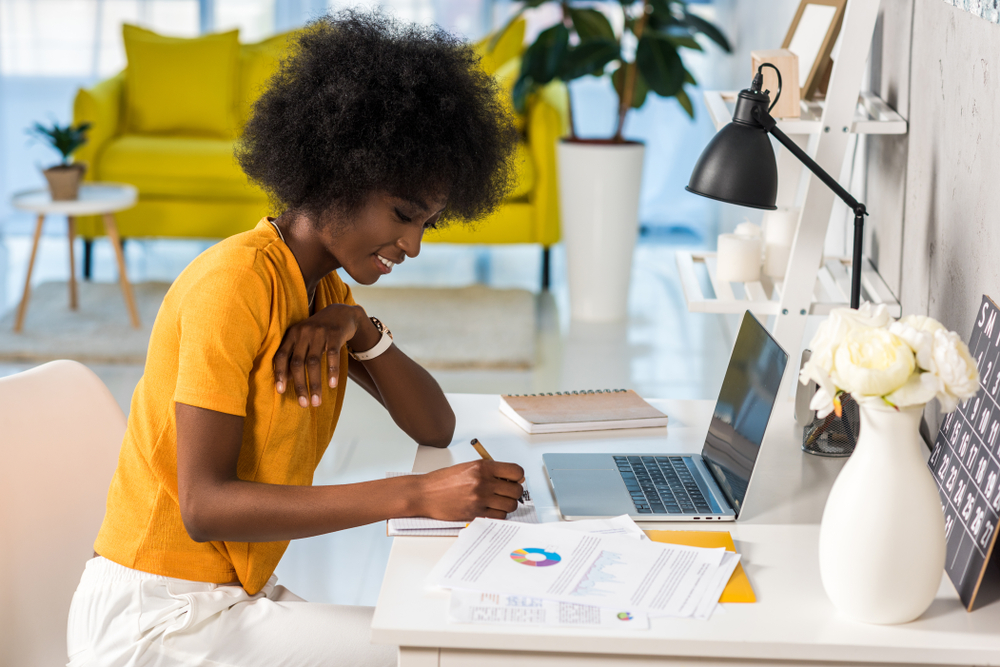 Shutterstock_1082417942 side view of smiling african american female freelancer working at home