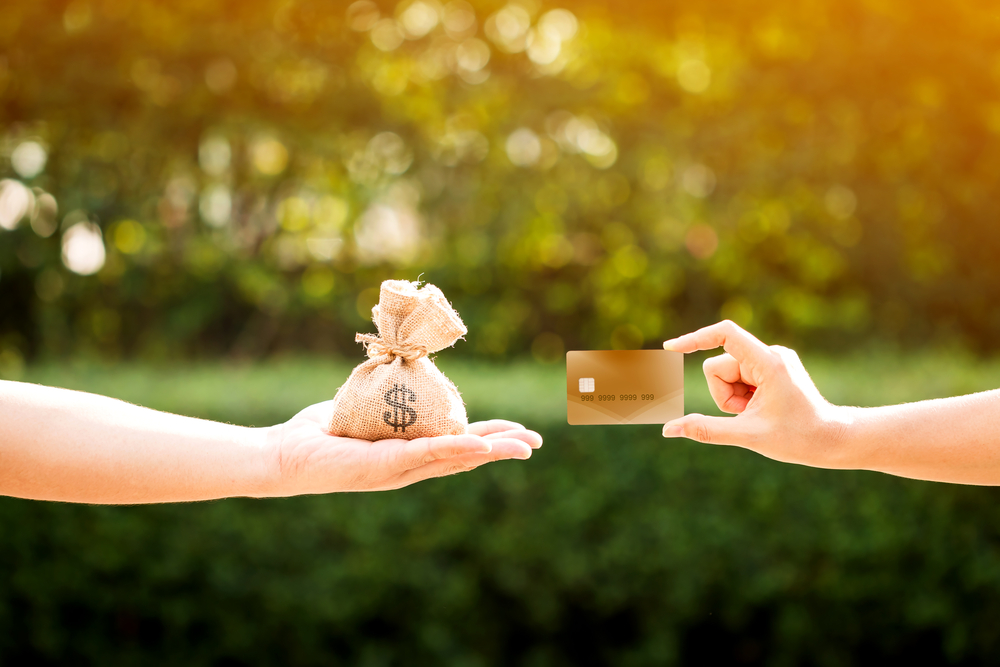 Shutterstock_675447955 A man and a women hand holding a money bag and credit card put together in the public park, loans to planned investment in the future concept.