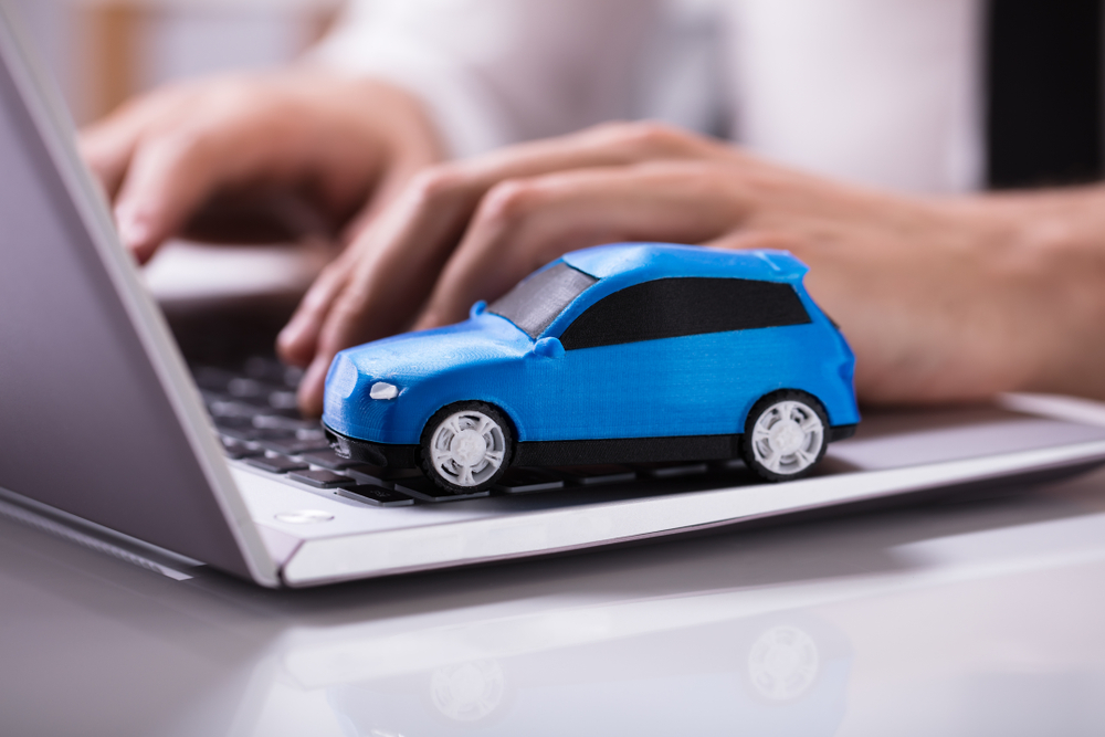 Shutterstock_1114214825 Close-up Of A Small Blue Car On Laptop Keypad