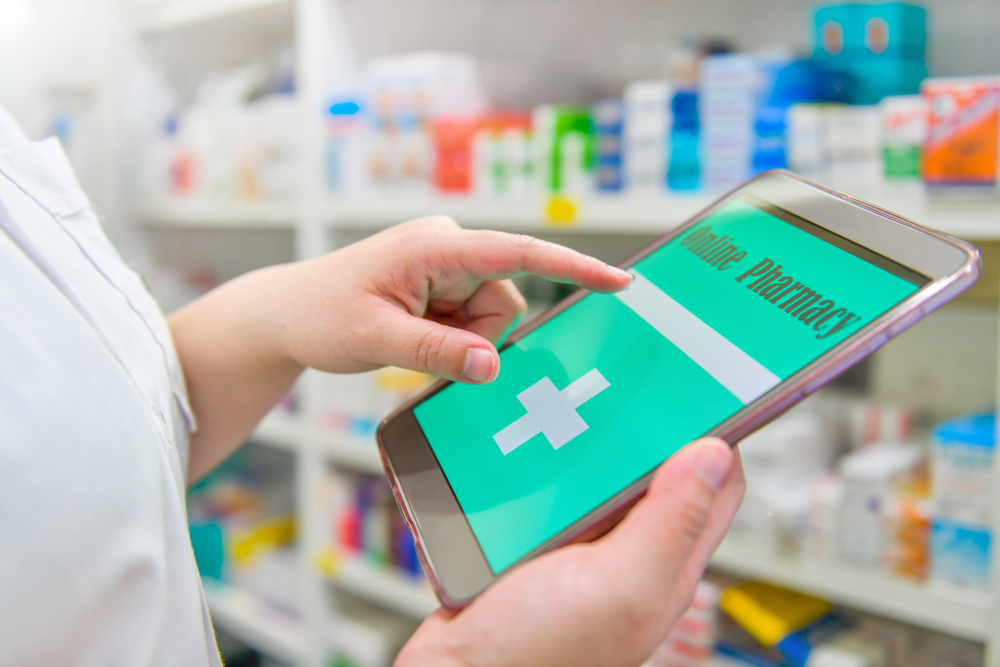 Shutterstock_1471304741 Pharmacist holding touchpad for search bar on display in pharmacy drugstore shelves background.Online medical concept.