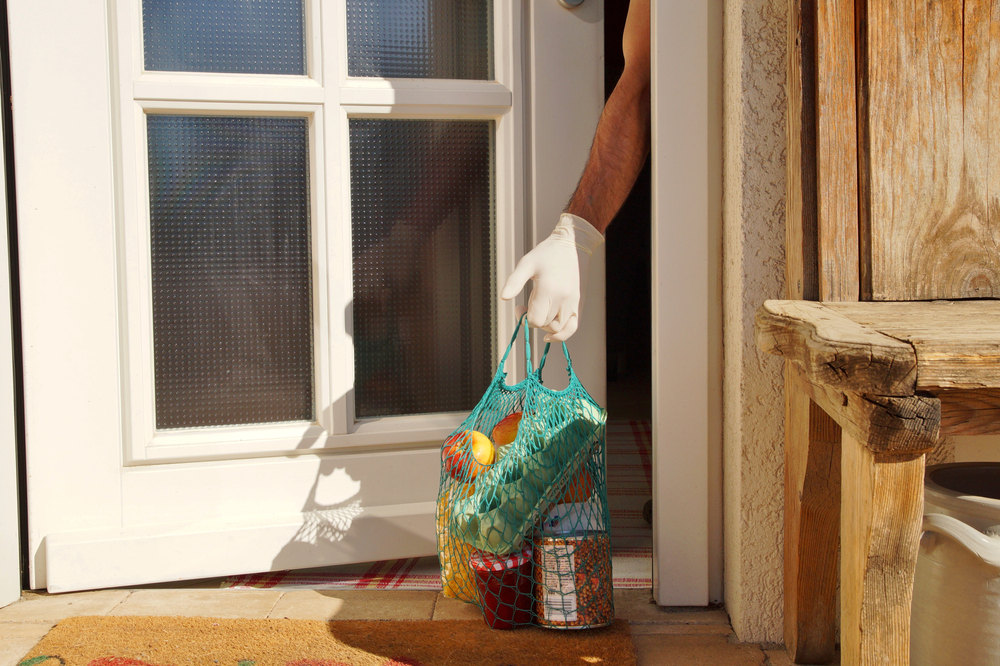 Shutterstock_1680124870 home delivering some groceries at quarantine time because of coronavirus infection COVID-19. man's hand is taking a shopping bag at he front door. Food delivery in net bag at door for self isolation