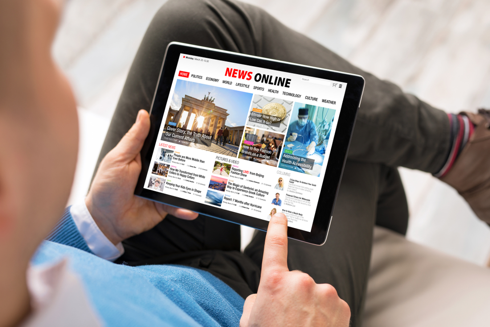 Shutterstock_1118068109 Man reading daily news online on tablet