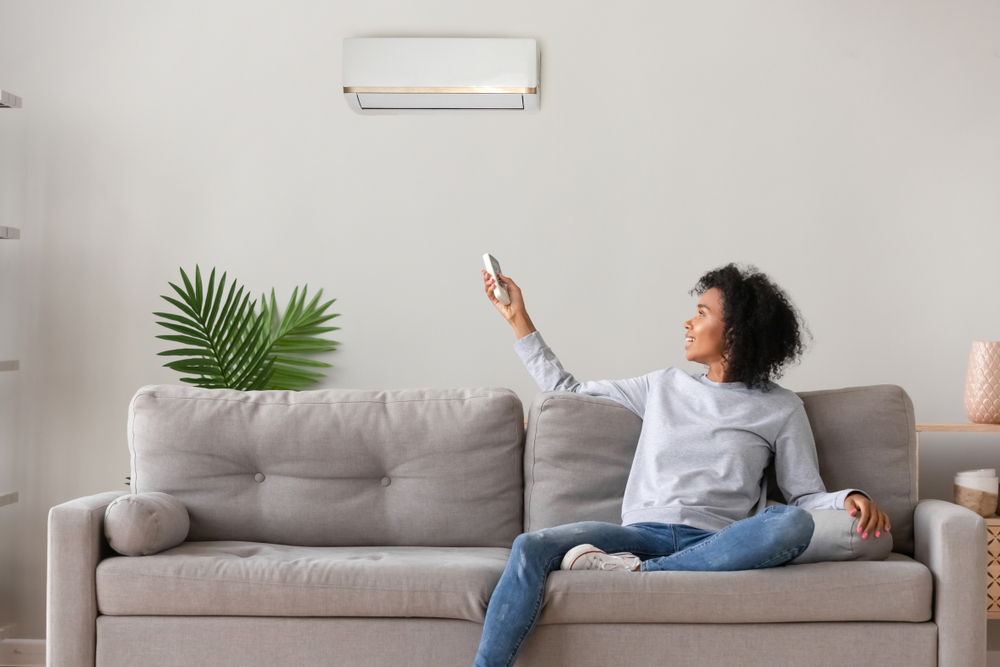 Shutterstock_1374932312 Smiling young African American woman using air conditioner, cooler system remote controller, switching, setting comfort temperature in living room, resting on cozy sofa at home, enjoy fresh air