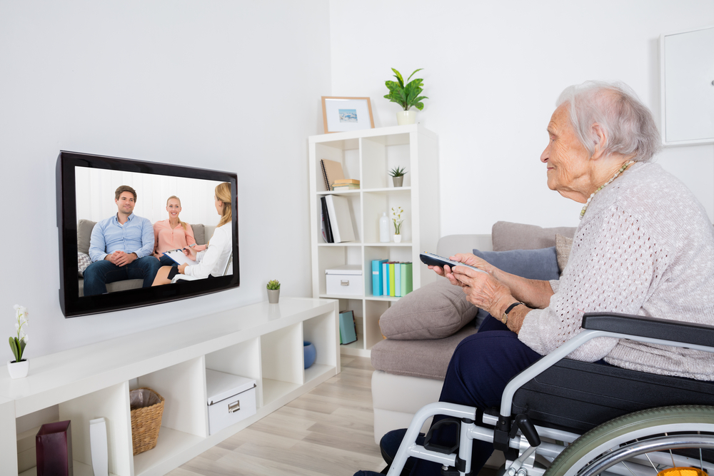 Shutterstock_495042715 Grandmother On Wheelchair Watching Movie On Television At Home