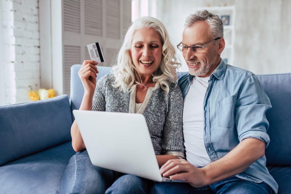 Shutterstock_1050674681 Love lives forever! Senior couple at home. Handsome old man and attractive old woman are spending time together. Sitting on a sofa with laptop and credit card in hands. Online shopping