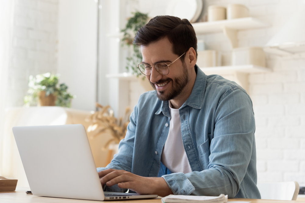Shutterstock_1575539239 Smiling young man freelancer using laptop studying online working from home, happy casual millennial guy typing on pc notebook surfing internet looking at screen enjoying distant job sit at table