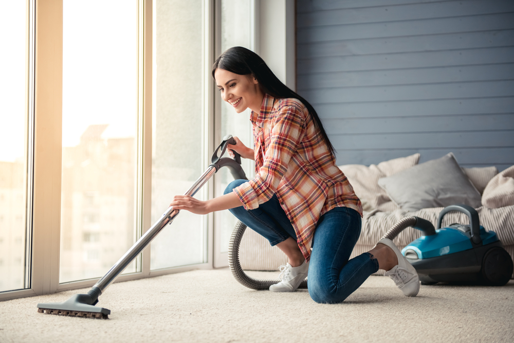 Shutterstock_572184355 Beautiful young woman is smiling and using a vacuum cleaner while cleaning floor at home