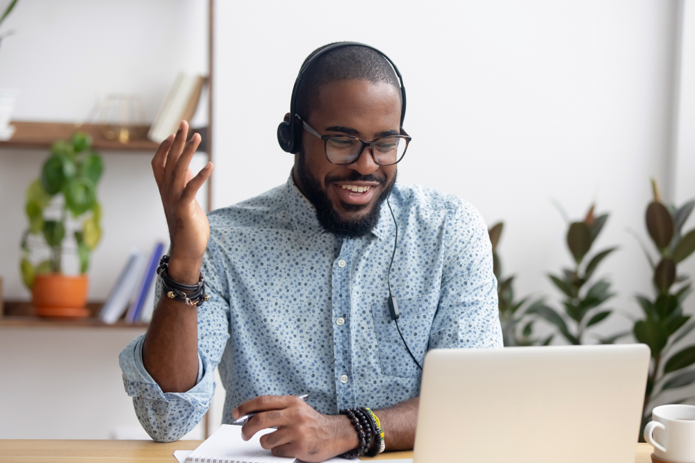 Shutterstock_1339292591 Smiling African American employee in headphones using laptop, looking at screen, making video call or watching webinar, writing notes, distance learning language concept, call center operator working