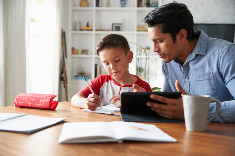 Shutterstock_1284992692 Hispanic pre-teen boy sitting at dining table working with his home school tutor