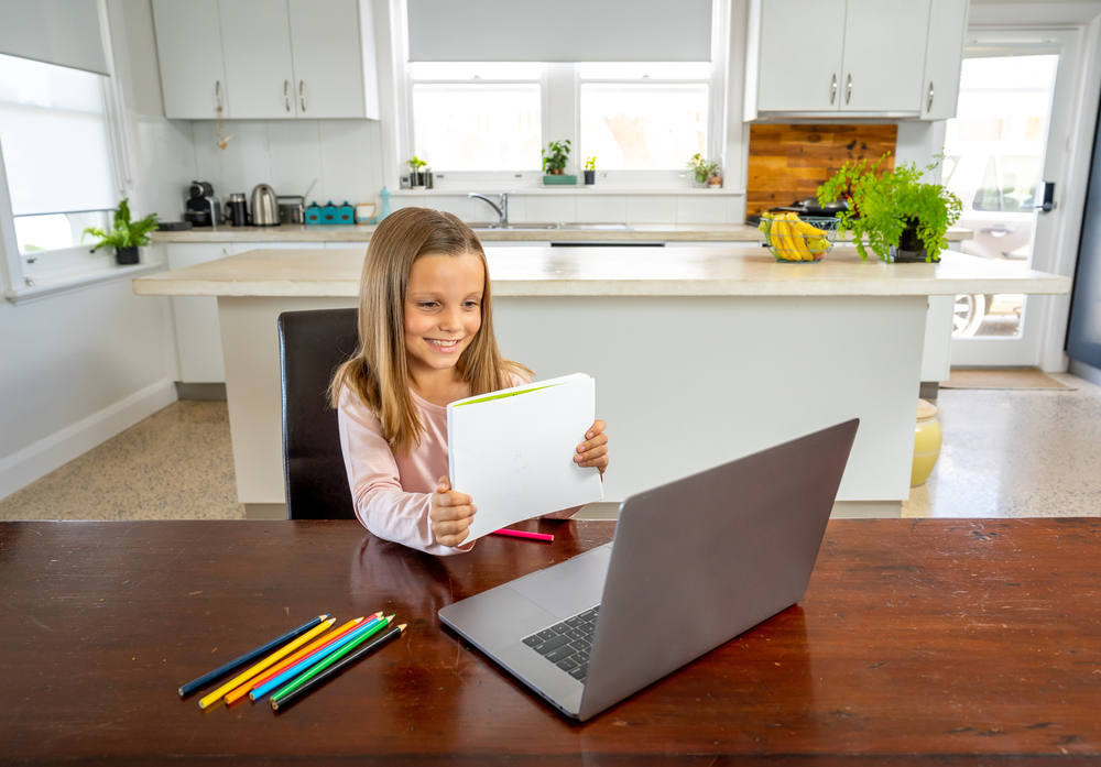 Shutterstock_1676759164 Coronavirus Outbreak. Lockdown and school closures. Schoolgirl watching online education class, happy talking with teacher on the internet at home. COVID-19 pandemic forces children online learning.